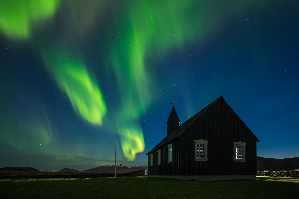 icelandic wooden house with the northen lights shining behind it