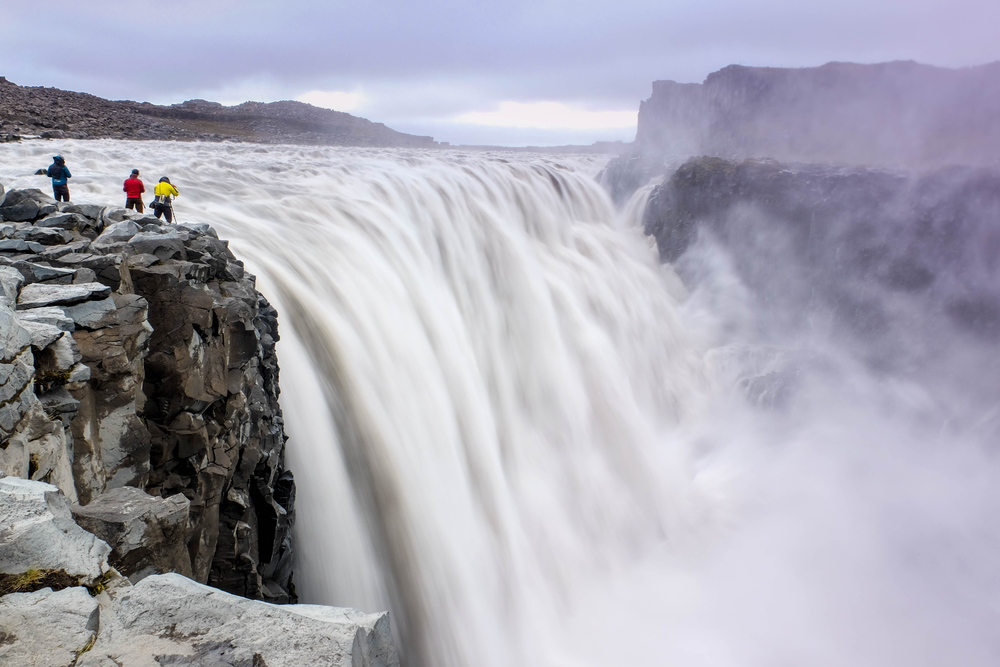 tourist enjoying the powerful and mighty dettifoss waterfall