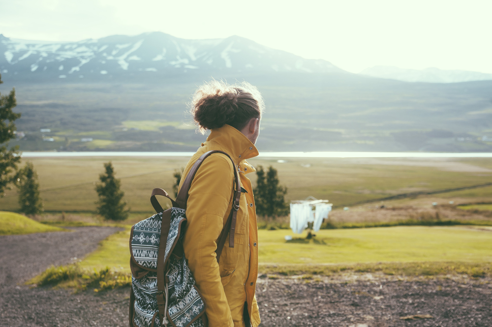 Girl with a yellow jacket looking at the green pastures of Iceland in June