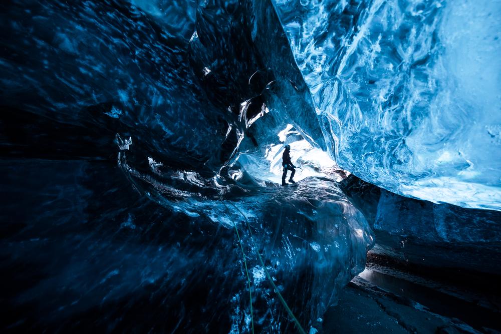 explorador en una cueva cueva de hielo en tonos azulados de Islandia