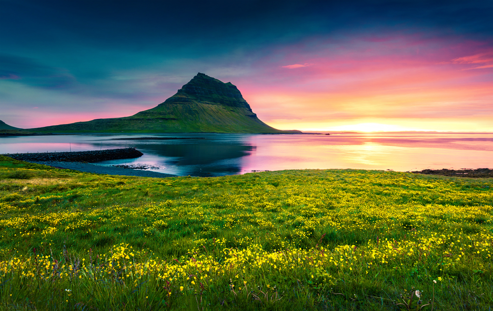 Kirkjufell mountain with a setting sun on the horizon of a beautiful june day in iceland