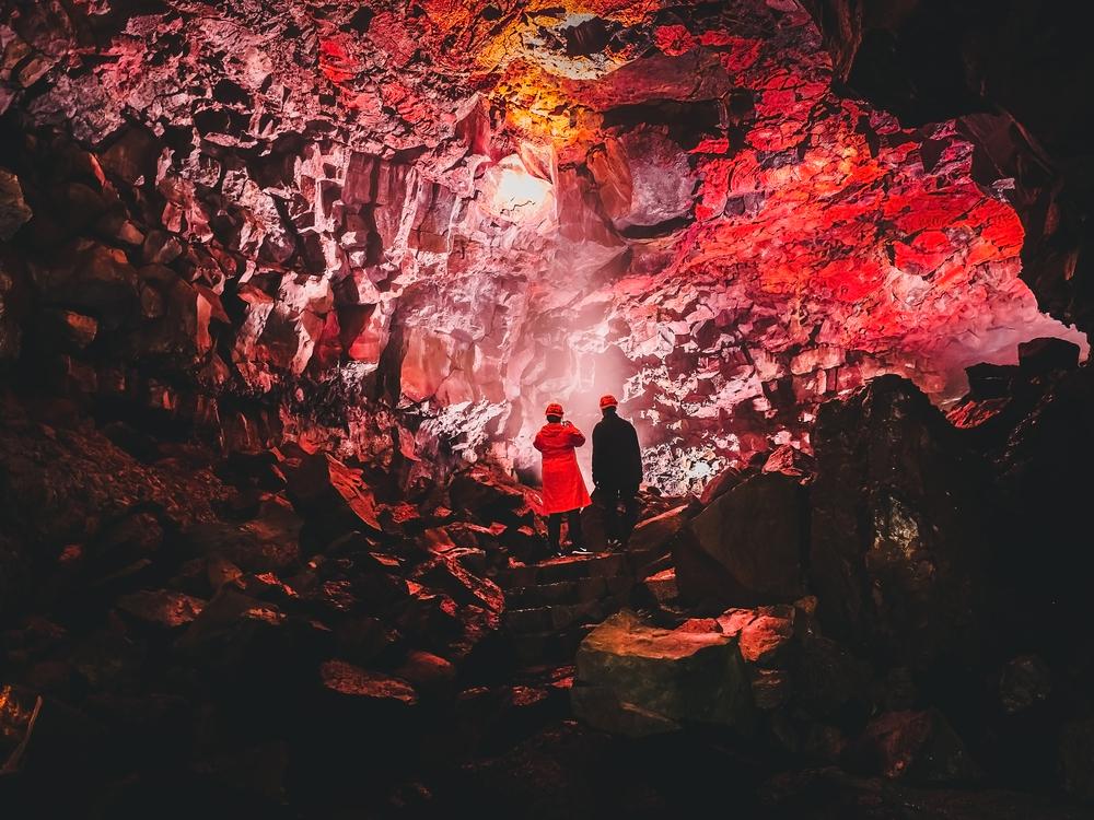 Pareja en medio de un tunel de una cueva de lava en Reykjavik