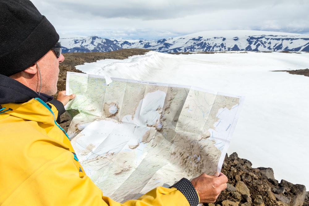 Hombre con chaqueta amarilla y un mapa para guiarse por las cuevas de Islandia