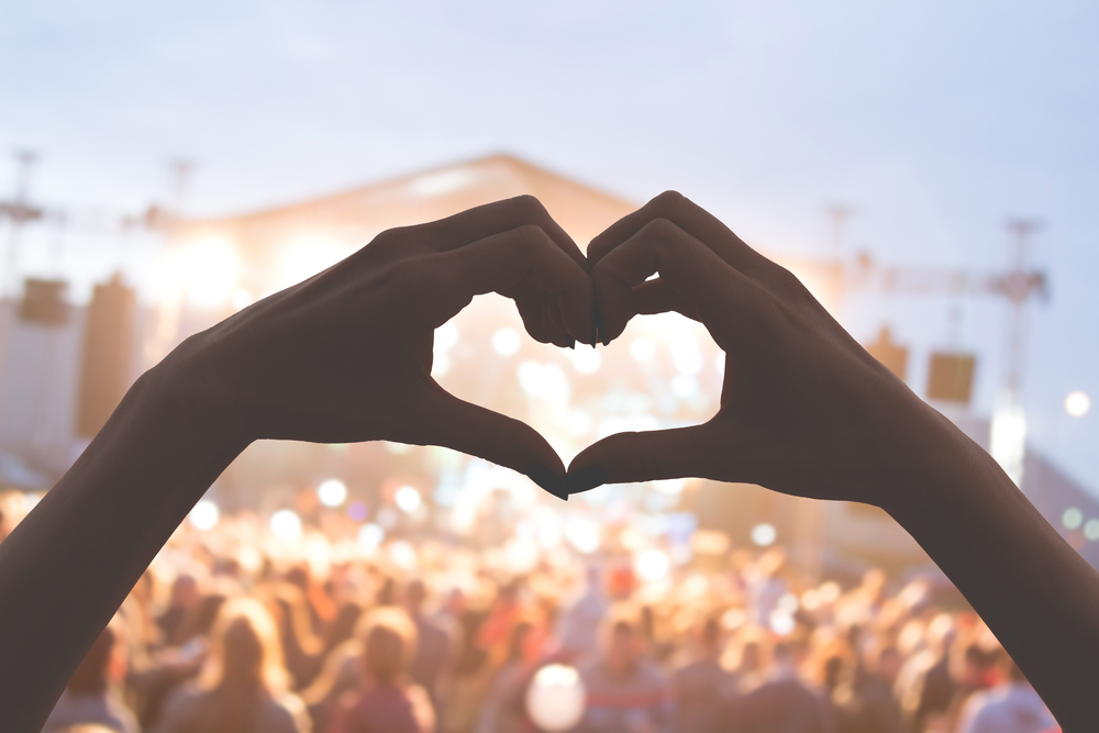 Two hands form a heart shape with a huge concert crowd on the back in a june music festival