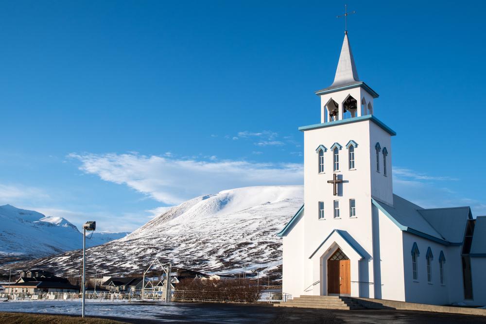 Iglesia pintada en blanco y azul al margen del fiordo con las montañas a sus espaldas