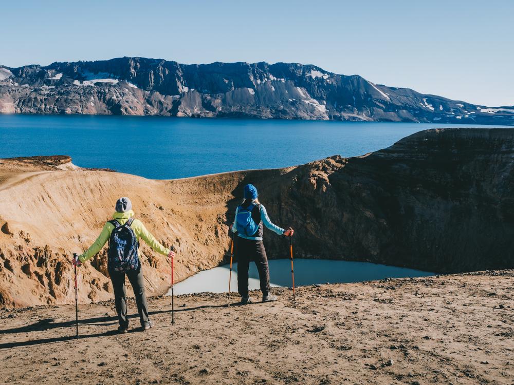Dos turistas haciendo trekking en el crater de askja aún abierto en septiembre en Islandia