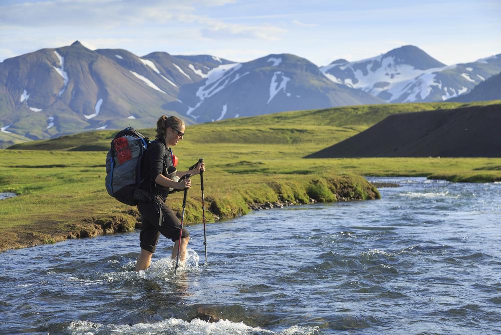 Mujer cruzando un rio en medio de la ruta de Laugavegur