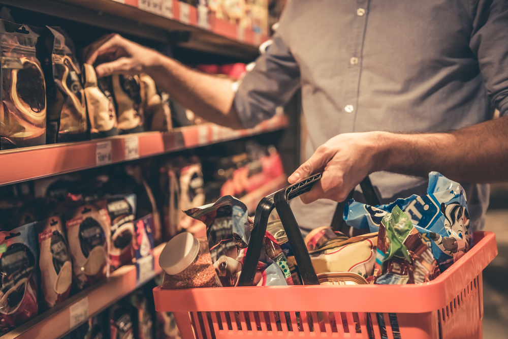 Hombre comprando en un supermercado 24h, deberías evitarlo cuando estés en Islandia