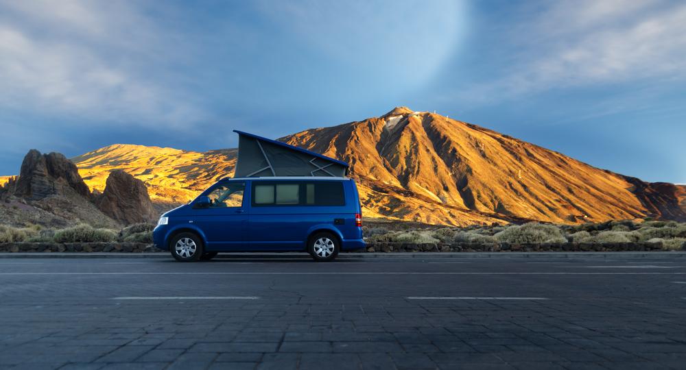 Camper en medio de la carretera con montañas al fondo, es una de las formas de mantener un presupuesto bajo