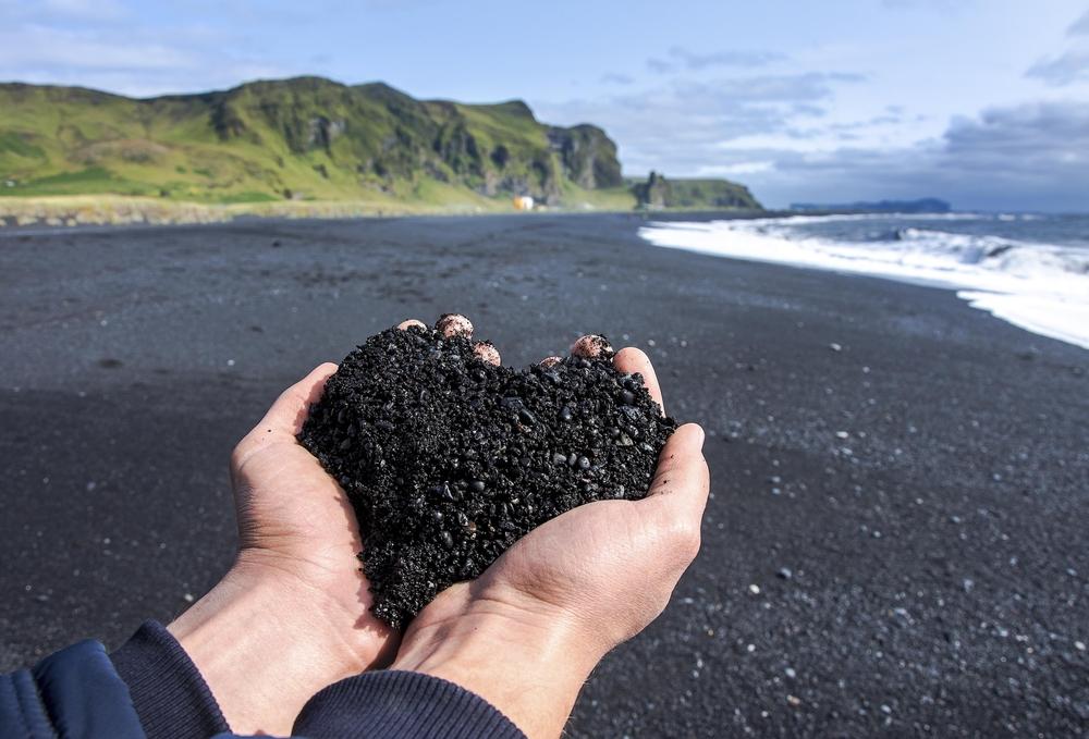 Visitante sujetando la arena negra de las playas de Vík