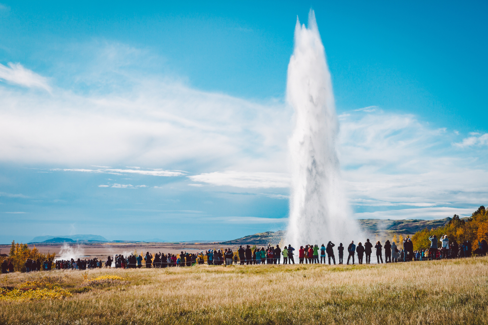 Grupo de turistas guiados a geysir como forma de turismo responsable en Islandia
