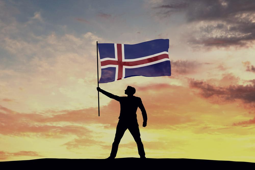 Hombre sujetando la bandera de Islandia, una nación con una forma peculiar de ver la vida