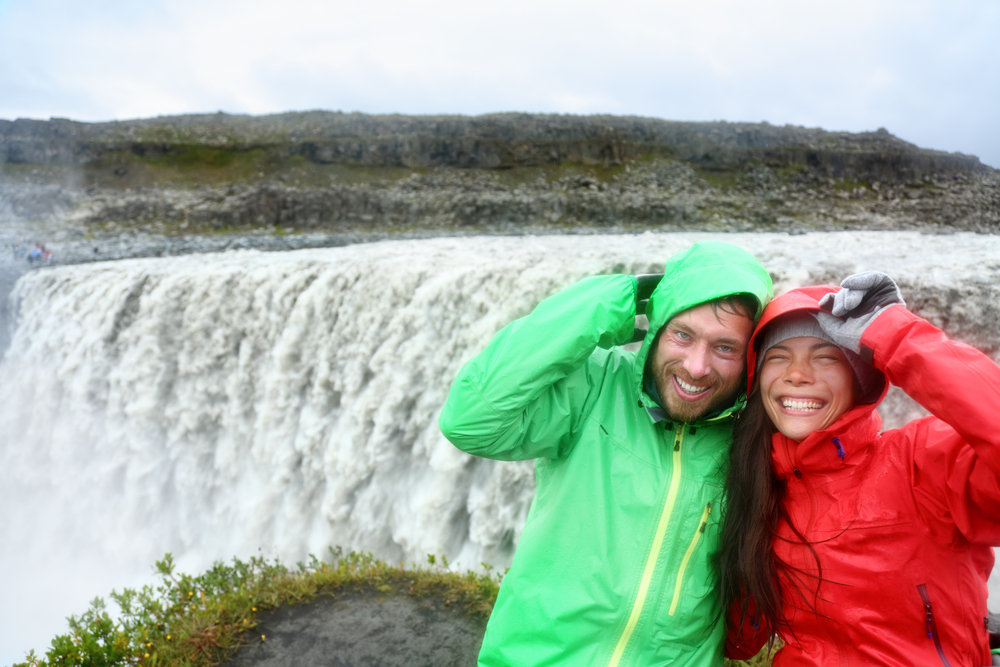 Pareja con chubasqueros para el tiempo húmedo en octubre en Islandia