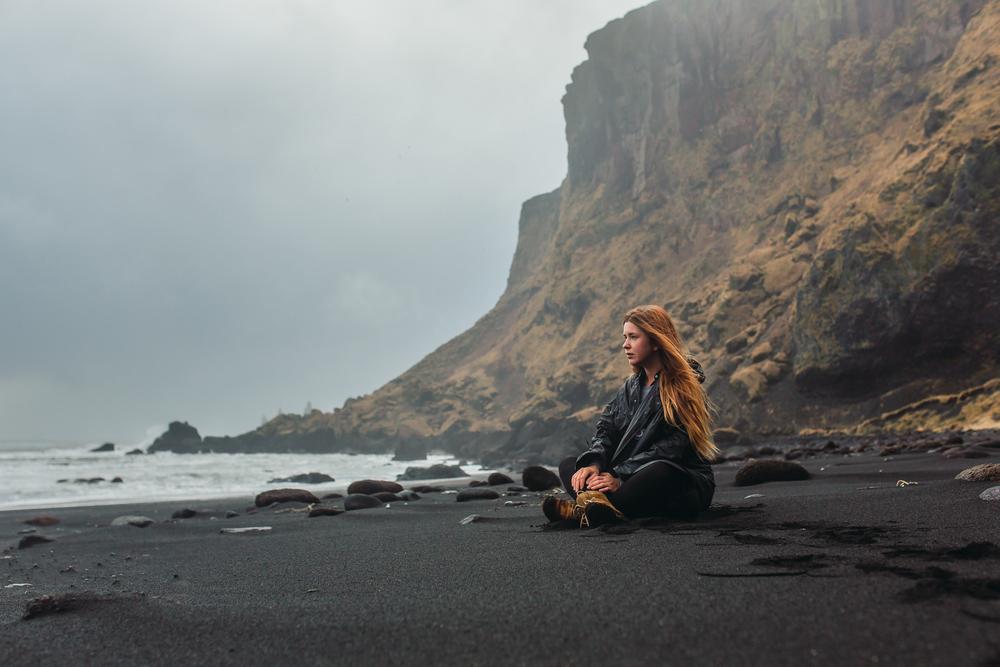 Chica viajando sola por Islandia disfrutando de las playas negras