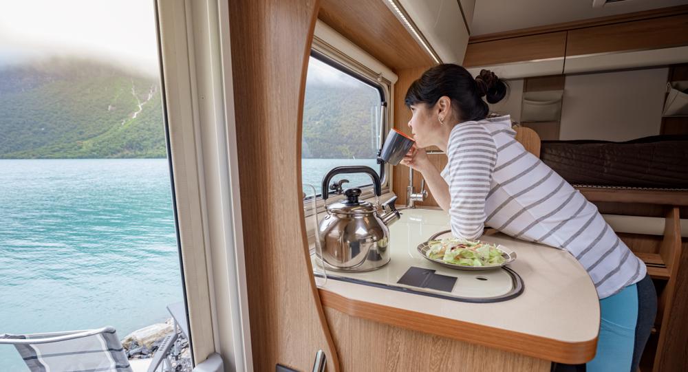 Chica disfrutando las vistas desde su autocaravana de alquiler en Islandia