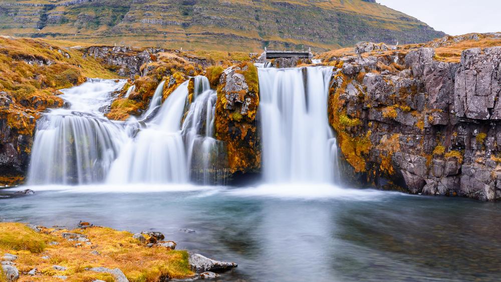 Preciosa cascada con vegetación típica del otoño en Islandia