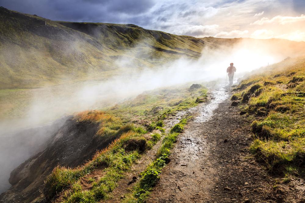 turista paseando por las fuentes termales de Reykjadalur