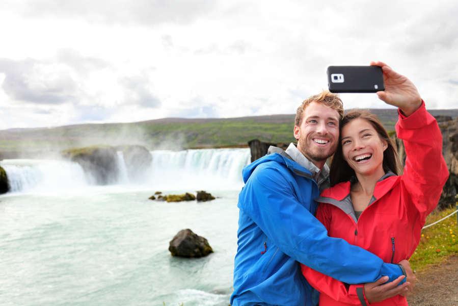 Pareja usando las redes moviles de islandia y tomandose una foto en una cascada